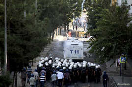 Kurdish protesters throw stones as they clash with riot police (foreground) in Diyarbakir, Turkey, Oct. 8, 2014.