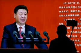 A man takes a selfie near a picture of Chinese President Xi Jinping on display at an exhibition on the Long March at the military museum in Beijing, Oct. 24, 2016.
