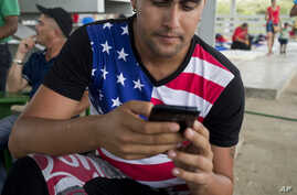 Cuban migrant wearing a t-shirt with a US flag design, uses his cell phone at a shelter in La Cruz, Costa Rica, border with Nicaragua.