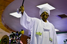 President Omar al-Bashir raises his arm as his supporters cheer at his victory speech after he won the presidential election at the National Congress Party headquarters in Khartoum, Sudan, April 27, 2015.