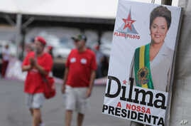 """People walk next to an official photography of Brazil's suspended President Dilma Rousseff, with a text written in Portuguese that reads """"Dilma our president,"""" at a camp in Brasilia, Brazil, Sunday, Aug. 28, 2016."""