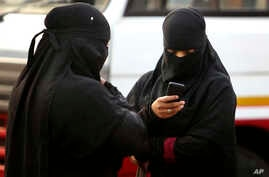 A burqa clad Indian woman checks her phone at a street in Hyderabad, India, March 24, 2015.