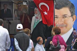 People walk past a poster of Turkey's Prime Minister and leader of the Justice and Development Party (AKP) Ahmet Davutoglu (R) in Istanbul, Turkey, June 5, 2015.