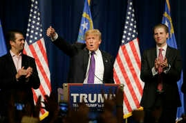Republican presidential candidate Donald Trump, is flanked by his two sons, Donald Trump Jr., left, and Eric, while speaking at a caucus night rally Tuesday, Feb. 23, 2016.