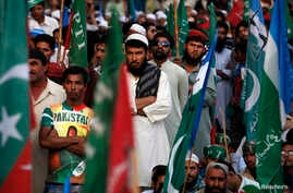Supporters of Pakistani religious party Jamaat-e-Islami (JI) and the Pakistan Tehreek-e-Insaf (PTI) political party of former cricket star Imran Khan, listen to their leaders speak during a protest in Karachi, Nov. 24, 2013.