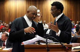 Advocate Dali Mpofu (L) reacts as he chats to Advocate Tembeka Ngcukaitobi during court hearing arguments on a report into allegations of political interference by wealthy friends of President Jacob Zuma, at the North Gauteng High Court, in Pretoria,...