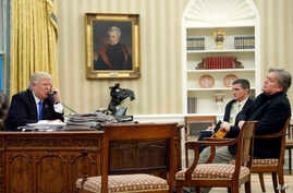 President Donald Trump speaks on the phone with Prime Minister of Australia Malcolm Turnbull, with National Security Adviser Michael Flynn, center, and chief strategist Steve Bannon, right, in the Oval Office of the White House, Jan. 28, 2017 in Wash...