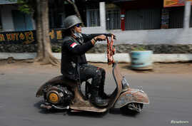 FILE - An extreme Vespa enthusiast rides his bike after attending weekend festival for extreme Vespas in Semarang, Central Java, Indonesia, July 22, 2018.
