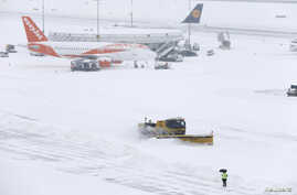 A snowplow removes snow next to EasyJet and Lufhansa aircraft during a temporary closure at Cointrin airport in Geneva, Switzerland, March 1, 2018.