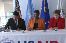 """From left to right: USAID Administrator Rajiv Shah, UN Emergency Relief Coordinator Valerie Amos and EU Humanitarian Commissioner Kristalina Georgieva sign a """"call to action"""" aimed at averting famine in South Sudan."""