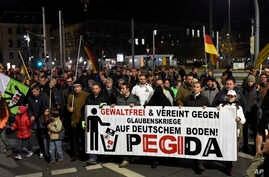 "FILE - Protesters hold a banner reading ""Without violence and united against religious wars on German soil - Pegida"" during a rally in Dresden, eastern Germany, Nov. 2, 2015."