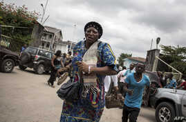 A Congolese woman runs for cover after police fired warning shots to disperse a crowd at the end of a Catholic service that commemorates the victims of a crackdown on last month's march on Jan. 12, 2018 in Kinshasa.