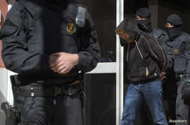 Regional police officers detain a man during a raid in one of the region's biggest operations against jihadi activity, in Sabadell, near Barcelona, Spain, April 8, 2015. (Reuters)