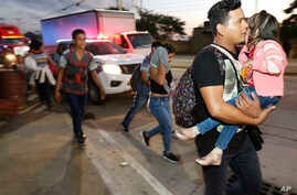 U.S.-bound migrants walk along the roadside as they leave San Pedro Sula, Honduras, at dawn Tuesday, Jan. 15, 2019. Yet another caravan of Central American migrants set out overnight from Honduras, seeking to reach the U.S. border, following the same