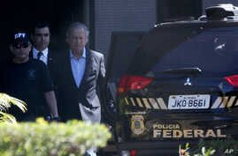 Jose Dirceu, former presidential chief of staff, center, is accompanied by federal police agents to a car at a police station in Brasilia, Aug. 4, 2015.