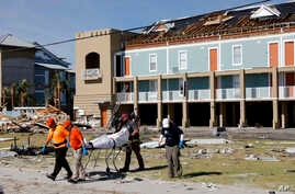 A body is removed after being discovered during a search of a housing structure in the aftermath of Hurricane Michael in Mexico Beach, Florida, Oct. 12, 2018.