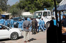 Somali police cadets arrive to help carry away the dead and injured following a suicide bomb attack on a police academy in the capital Mogadishu, Somalia, Dec. 14, 2017.