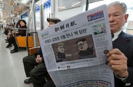 A passenger reads a newspaper with headline of a planned summit meeting between North Korean leader Kim Jong Un and U.S. President Donald Trump, left, at subway train in Seoul, South Korea, March 10, 2018. The White House tried to swat away criticism