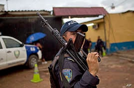A member of the Honduran National Police outside a police station near El Mayoreo markert in Tegucigalpa, Honduras, June 1, 2013.