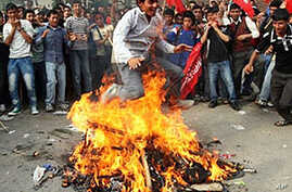 A Unified Communist Party of Nepal (Maoist) supporter jumps over a fire with a burining effigy of prime minister Madhav Kumar Nepal during the fourth day of indefinite strike in Kathmandu, 05 May 2010