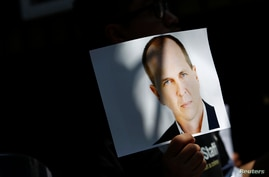 A demonstrator holds up a photograph of Australian national and correspondent of Al Jazeera Peter Greste during a protest outside the Egyptian embassy in Mexico City, Feb. 27, 2014.