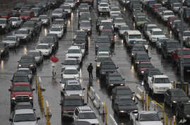 FILE -Cars wait to enter the United States from Tijuana, Mexico through the San Ysidro port of entry in San Diego, Dec. 25, 2014.