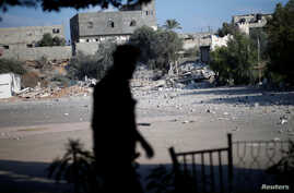 FILE - A member of Palestinian Hamas security forces walks past a Hamas site that was hit in an Israeli airstrike, in Al-Mughraqa on the outskirts of Gaza City, Aug. 9, 2018.