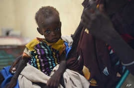 Nyagoah Taka Gatluak, a severely malnourished 1-year-old child, sits on her mother's lap in the Doctors Without Borders clinic in Leer town, South Sudan, Dec. 15,  2015 — the two-year anniversary of the beginning of South Sudan's civil war.