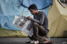 An earthquake survivor reads a newspaper at a shelter camp in Kathmandu, April 29, 2015.