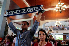 An anti-government protester holds a scarf with the name of Nicaragua during a Palm Sunday Mass in Esquipulas, Nicaragua, April 14, 2019.