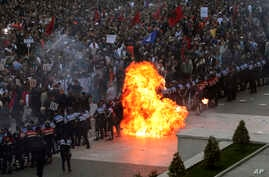 Flames rise from a petrol bomb thrown toward a police line that was blocking anti-government protesters at a rally in Tirana, Albania, May 11, 2019. Protesters demand that the Socialist government resign and call an early parliamentary election.
