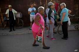Pura Castell walks to a government-run butcher shop to buy chicken, after failing to find chicken the previous day in Bauta, Cuba, April 12, 2019.