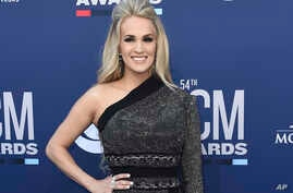 FILE - Carrie Underwood poses for photos at the 54th annual Academy of Country Music Awards in Las Vegas, April 7, 2019.