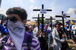 Anti-government protesters join a Stations of the Cross procession on Good Friday, carrying signs demanding the release of political prisoners in Managua, Nicaragua, April 19, 2019.