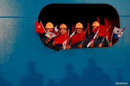 FILE - Sailors wave the China and Panama flags to China's President Xi Jinping at the Cocoli locks in the expanded Panama Canal, in Panama City, Panama, Dec. 3, 2018.