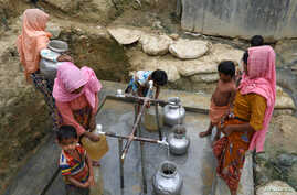 FILE - Rohingya refugees collect drinking water at the Shalbagan refugee camp in Teknaf, Bangladesh, March 5, 2019.