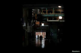 A worker walks next to halted machines at a cans' factory during a power cut in Valencia, Venezuela, April 8, 2019.