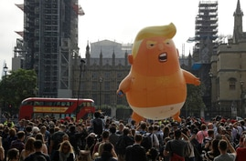 A six-meter high cartoon baby blimp of U.S. President Donald Trump is flown as a protest against his visit, in Parliament Square backdropped by the scaffolded Houses of Parliament and Big Ben in London, England, July 13, 2018. Trump is making his first trip to Britain as president after a tense summit with NATO leaders in Brussels and on the heels of ruptures in British Prime Minister Theresa May's government because of the crisis over Britain's exit from the European Union. (AP Photo/Matt Dunham)