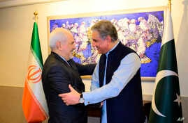 In this photo released by the Foreign Office, Pakistani Foreign Minister Shah Mehmood Qureshi, right, shakes hands with Iranian Foreign Minister Mohammad Javad Zarif at the Foreign Ministry in Islamabad, Pakistan, May 24, 2019.