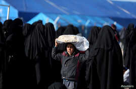A boy carries bread on his head at al-Hol displacement camp in Syria, April 2, 2019.