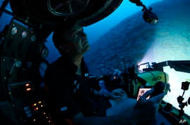 Submersible pilot Robert Carmichael looks out of the submersible as he navigates strong currents during a dive to 400 feet below the surface on Monday April 8, 2019.