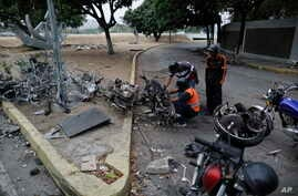 Men look to recover usable parts from motorcycles burned during the previous day's clashes between anti-government protesters and security forces in Caracas, Venezuela, Wednesday, May 1, 2019.