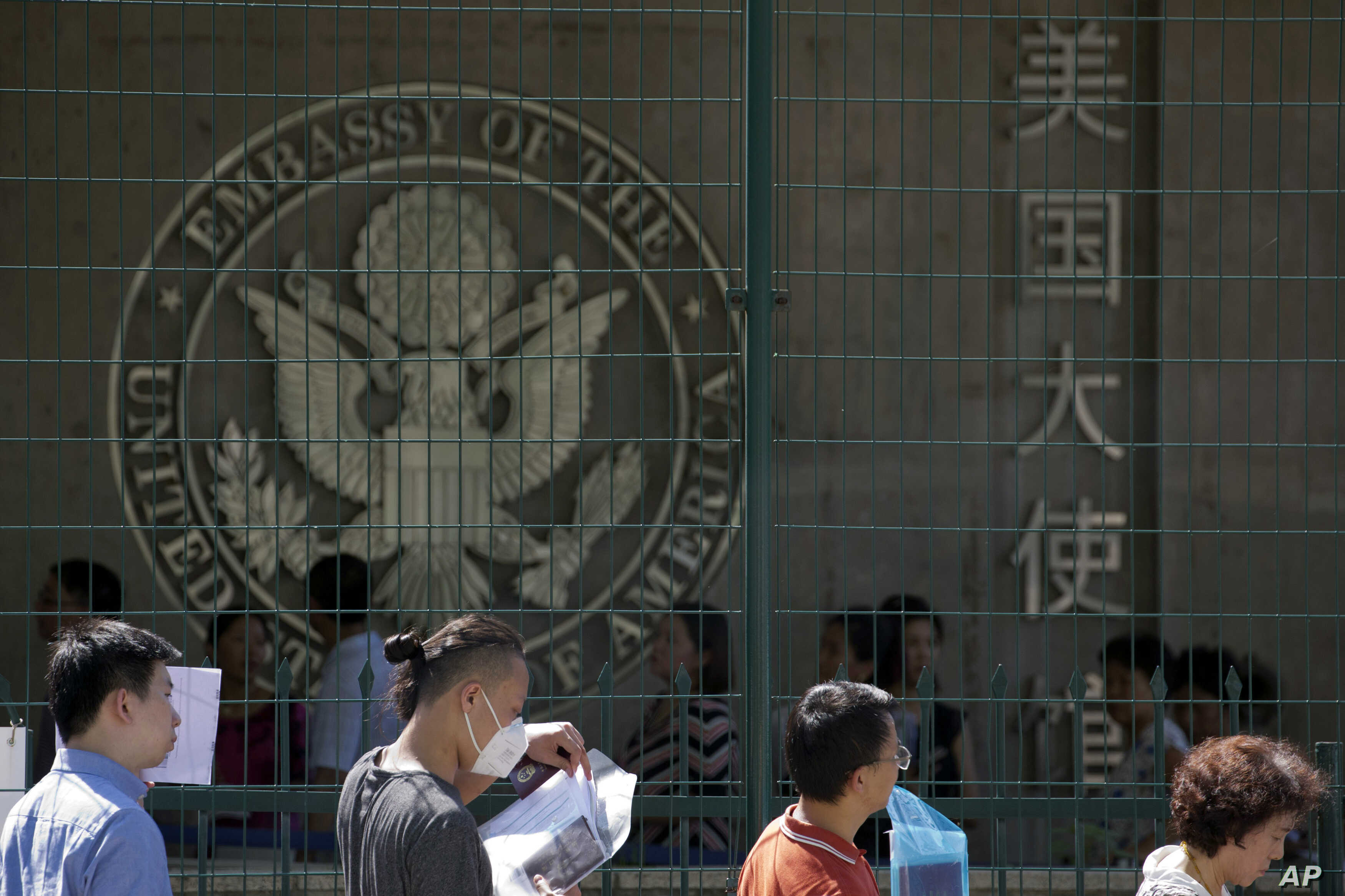 FILE - Visa applicants wait to enter the U.S. Embassy in Beijing, China, July 26, 2018.