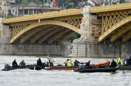Rescuers in boats work to prepare to recover a capsized boat under Margaret Bridge in Budapest, Hungary, Thursday, May 30, 2019. Rescue crews in Hungary's capital are preparing to raise a sightseeing boat from the bottom of the Danube River Thursday as search teams scoured the waters for 21 people missing after the vessel, packed with South Korean tourists, collided with a larger cruise ship and sank. Seven people are confirmed dead and seven were rescued, all of them South Koreans. (Zoltan Mathe/MTI via AP