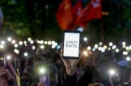 Demonstrators wave their cellphones as they protest plans to construct a cathedral in a park in Yekaterinburg, Russia, May 15, 2019.