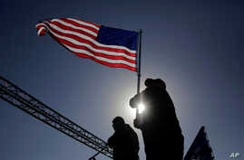 A man holds a American flag as supporters of President Donald Trump take part in the pledge as they stand in line for his rally outside the El Paso County Coliseum, Feb. 11, 2019, in El Paso, Texas.