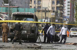 Health workers retrieve a body after an attack that targeted a bus carrying mostly government employees in Kabul, Afghanistan, June 3, 2019.