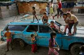 """Children play on top of an abandoned car at the """"Aguerridos Liberator"""" shanty town in Caracas, Venezuela, Thursday, May 9, 2019. In the fourth month of their standoff, Venezuela's President Nicolas Maduro and opposition leader Juan Guaidó are unable to deliver a knock-out blow as Venezuela spirals deeper into neglect, isolation and desperation. (AP Photo/Rodrigo Abd)"""