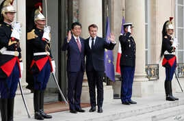 French President Emmanuel Macron, center right, and Japan's Prime Minister Shinzo Abe wave before their talks at the Elysee Palace, in Paris, April 23, 2019.