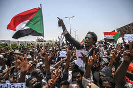 Sudanese protesters wave national flags as they chant slogans during an a sit-in outside the army headquarters in the capital Khartoum, April 26, 2019.